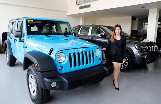 A sales worker poses between U.S. made Jeep Wrangler and Cherokee SUV, at a local dealer of U.S. made vehicles, Automotive Icon in Alabang