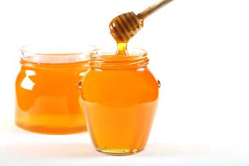 мёд свежий стоит в банке на белом фоне