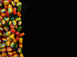 Colorful fruit gummy candies on black background. Top view with copy space.