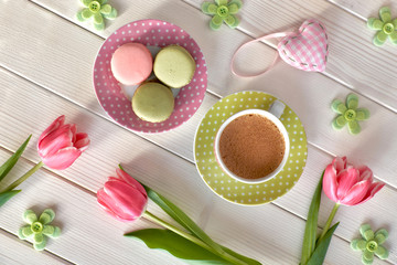 Spring coffee background. Macarons, espresso in pink cup, freesias and pink tulips