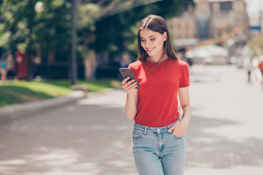 Fit girl smiling and looking into the phone holding her hand in