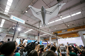 Visitors take pictures of a bionic flying fox at Festo's booth at the WRC in Beijing