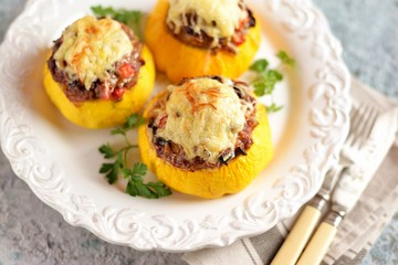 Organic yellow patissons stuffed with meat, onions, carrots, mushrooms and red pepper baked in the oven with cheese.