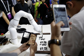 A seven-axis robotic arm writes Chinese calligraphy at Cheetah Mobile's booth at the WRC in Beijing
