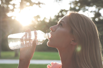 Beautiful young girl drinking water from a plastic bottle after a long walk in the woods