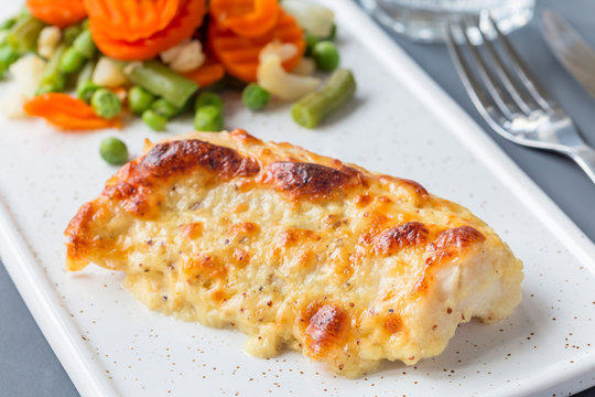 Baked cod fish fillet under cheese, mustard, pepper and cream crust, served with steamed vegetables, horizontal
