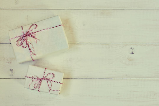 Vintage gift boxes on the shabby wooden background. Gift box wrapped white paper,  tied red & white baker twine with tag. Vintage Style. Background for your design. Holiday packing concept.
