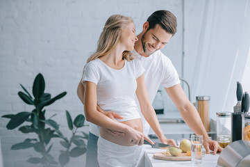 happy pregnant woman and husband cooking fruits salad together in kitchen at home