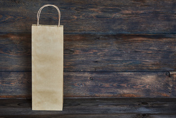 Sale, consumerism and advertisement concept -  blank  brown paper  bags on the vintage wooden board background. Paper bags with handles, blank craft shopping bag with area for your logo or design.
