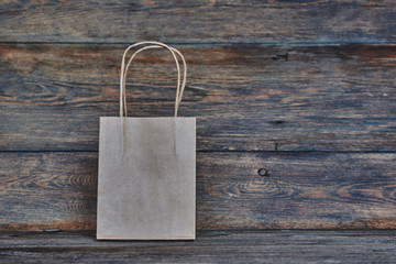 Mock-up of brown craft paper package with handles, empty shopping bag with area for your logo or design, wooden board in the background, food delivery, sale, consumerism and advertising concept.