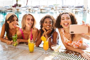 Four cheerful young women in swimwear taking a selfie