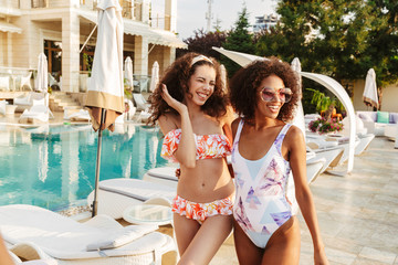 Image of two happy young women in swimwear standing together, having fun at the swimming pool outdoors