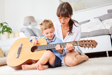 Junge lernt Gitarre spielen zu Hause