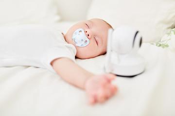 Baby schläft mit Babyphon am Babybett