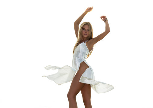 Beautiful young woman in a flowing satin dress stands and raising hands up in front a white background