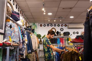 Cheerful man choosing clothing in shop