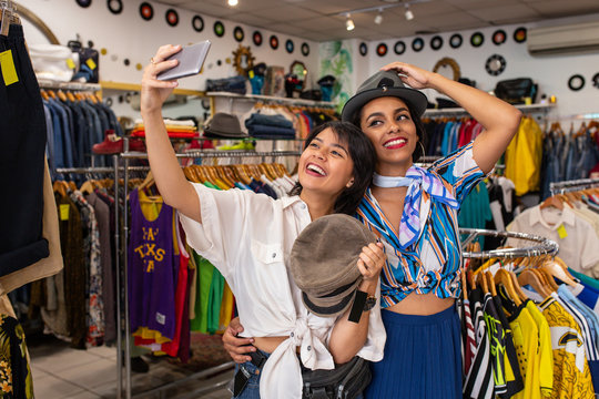 Cheerful friends trying on hat in shop and taking selfie