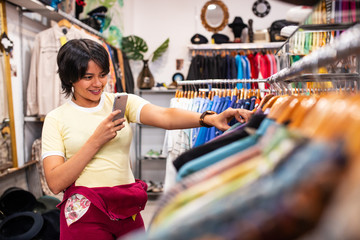Cheerful woman taking photos of clothes in shop
