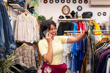 Cheerful woman talking by mobile in shop