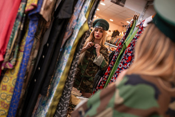 Woman trying on military outfit in shop