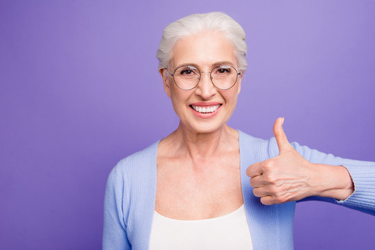 Portrait of grey haired old smiling confident woman wearing glas