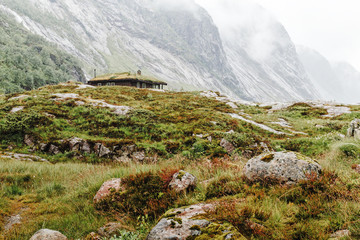 Wall Mural - Norway, Scandinavia. Single house in Norwegian mountains. Typical overcast misty weather for Scandinavian summer. Landscape photography. Green and brown color in nature.