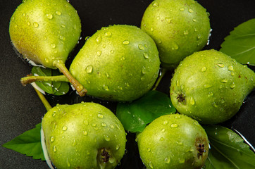 Green pears are splashed with drops of water