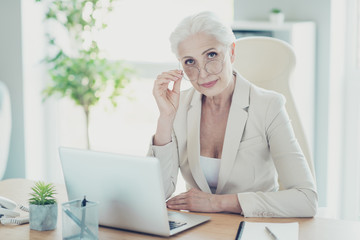 Grey-haired beautiful stylish old serious lady office executive