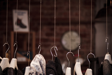 Many clothes hanger on chains with dark background in a shop