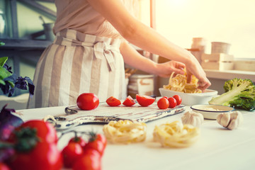 Close up of unrecognizable cook,cutting tomatoes and other vegetables with knife while working in home kitchen. Woman cooking salad, bio food preparing. Vegetarian food, health lifestyle concept.