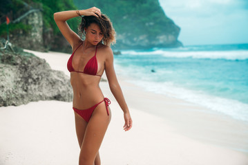 Young girl with a gorgeous body is resting on the beach with white sand near the ocean. Beautiful sexy model in a red bathing suit sunbathing. Brunette with curly hair in bikini.