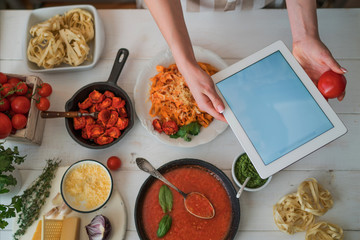 Young woman using a tablet computer to cook in her kitchen. Cook healthy food. Woman housewife cooks food a recipe from the Internet with a tablet computer in the kitchen. Soft focus.