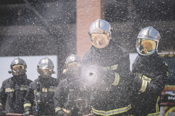 Working firemen throw water with hose.