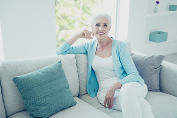 Charming elderly woman sitting on sofa in living room and lookin