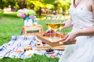 Young woman holding a dish with glasses white wine at picnic summer party, close up