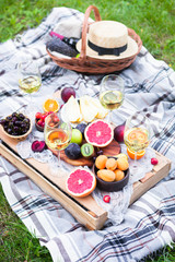 Aluminium Prints Picnic Picnic background with white wine and summer fruits on green grass, top view