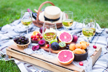 Fotobehang Picknick Picnic background with white wine and summer fruits on green grass, summertime party