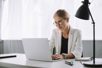 portrait of businesswoman working on laptop at workplace in office
