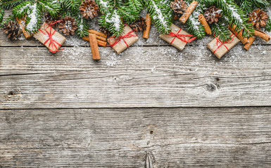 Holiday decoration - christmas border with fir tree branches and gift boxes on wooden background