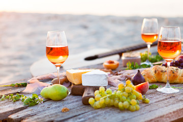 Picnic on beach at sunset in boho style. Romantic dinner, friends party, summertime, food and drink concept