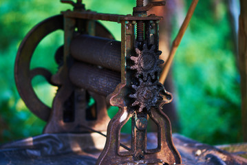 Abandoned palm oil press. Old iron press for pressing palm oil in green landscape.