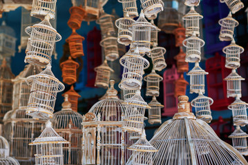 Many different sizes, colorful, wooden cages for birds. The store for selling cages for birds is completely filled with various colorful handmade cages.  Multicolored background. Selective focus.