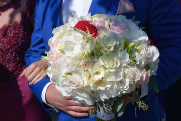 Cropped shot of Caucasian young male guest or groom at wedding, wearing a royal blue suit and holding a beautiful mixed bouquet featuring white and pale pink roses, freesias and white hydrangeas