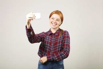 Portrait of playful redhead woman wearing flannel checkered shirt taking a selfie with mobile phone, isolated grey background. Female student holding smartphone, taking pictures. Copy space, close up.