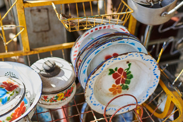 Set of old kitchen tools. Retro equipment of cooking. Various objects for sale at a indoor flea market. View of a display full of interesting old things for sale. Vintage assorted second-hand objects.