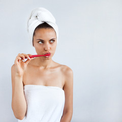 Smiling happy young woman with healthy teeth holding a tooth brush. Clean beauty and healthy concept