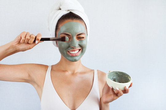 Young beautiful woman in face mask of therapeutic blue mud. Spa treatment, self care and healthy skin