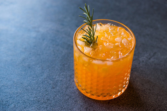 Carrot Cocktail with Crushed Ice and Rosemary.