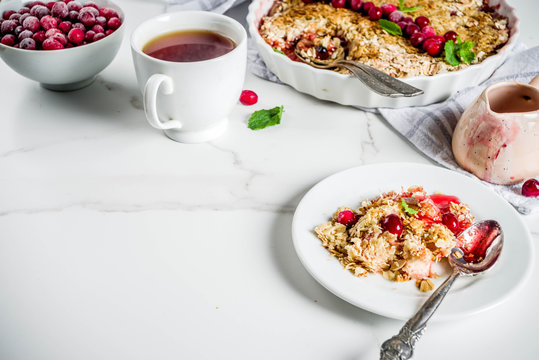 Traditional autumn winter pastries, homemade pie crumble with apples and cranberries, on a white marble table, copy space for text
