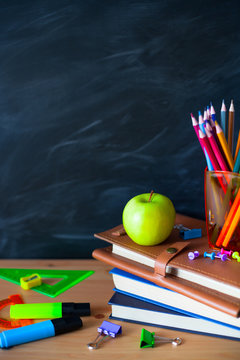 Back to School cocept. Still life with school books, pencils and apple against blackboard background